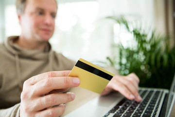 Happy adult man sitting at home on couch with smart phone and credit card. Paying bills and orders. Online shopping and e-commerce concept.