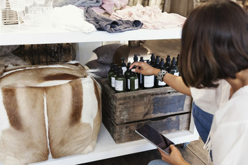 Owner using digital tablet while checking bottles on shelf at store