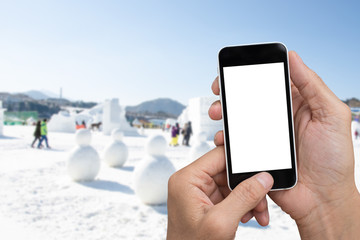 Man hands holding smartphone with winter background.