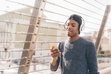 Young handsome american african man listening music with head phones and smart phone hand hold outdoor in back light city - music, technology, social network concept