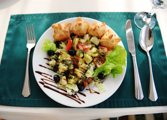 Greek salad on a white plate. Served on a table with a green tablecloth in a restaurant