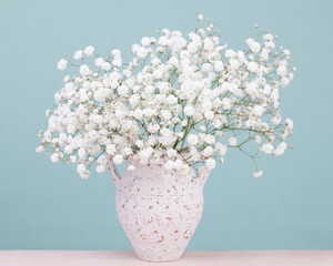 Bouquet of white tiny baby's-breath flowers in an antique cerami