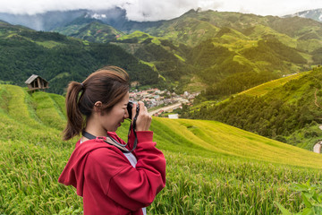 female adventure traveler taking a photo at the nice view of Mu Cang Chai, Vietnam.