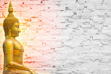 Golden Buddha glow with brick wall background or postcard or wallpaper design.
