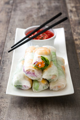 Vietnamese rolls with vegetables, rice noodles and prawns on wooden background