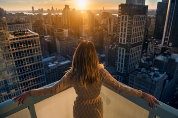 Rich woman enjoy the sunset standing on the balcony at luxury apartments in New York City. Luxury life concept. Succesful B.businesswoman relax. Wall mural