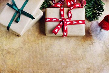 Vista aérea de cajas para regalo con empaquetado rústico, cinta roja con corazones y cinta verde, elfo  y una rama de abeto. Imagen texturizada con fondo abstracto y espacio vacío para publicidad.