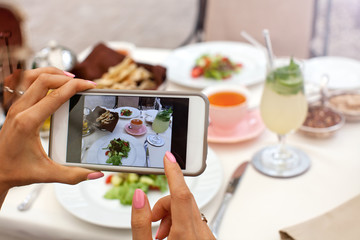 Woman photographing food served in restaurant with mobile phone.