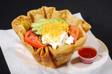 Taco salad, sour crrean, avocado, tomato and cheese in a shell