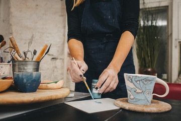 Female hands working on mug