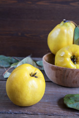 The fresh quince fruit on dark wooden table. An autumn still life.
