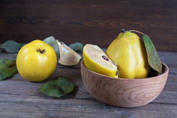 The fresh quince fruit on dark wooden table. An autumn still life.