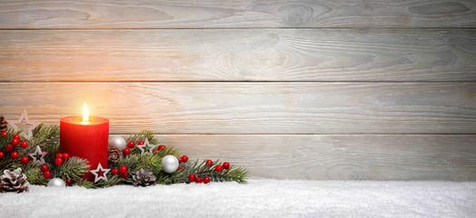 Weihnachten oder Advent Hintergrund: Holz, eine Kerze und Tannenzweige auf Schnee, Panorama Format mit Textfreiraum