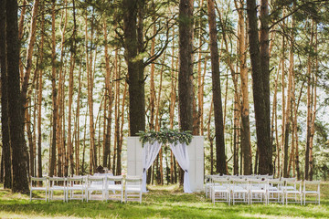 Beautiful white color outside decor for wedding ceremony in scenic place in old wood. White arch decorated with fresh flowers and rows of many wooden chairs at high pine trees background.