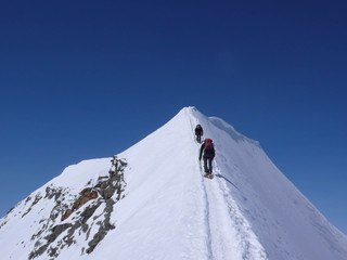 two mountain climbers on an exposed ridge in the Swiss Alps