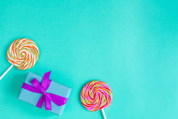 rainbow candy and gift box on blue background