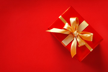 Red gift with golden bow on red background. Close up. Top view. High resolution product