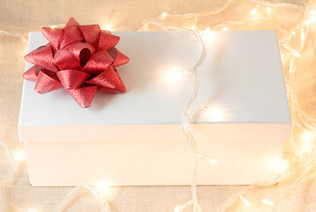 White gift box with red bow and ribbon with garland and many lights