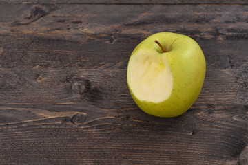 One bitten green apple on a brown wooden desk, top angle view