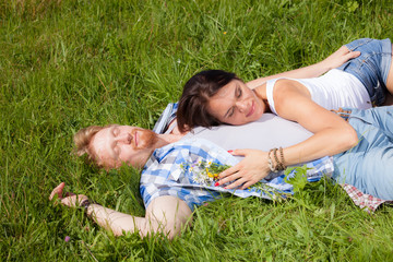 Happy beautiful couple in love lying on the green grass meadow