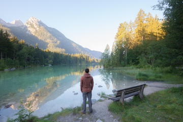Man standing near the mountain lake at sunny morning