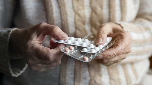 closeup of old female hands holding pills