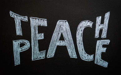 Teach peace written on a chalkboard. Peace concept