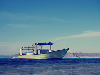 Fishing boat at the blue sea, retro hipster style