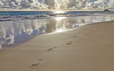 Footprints and footsteps on the sand tropical beach sunrise