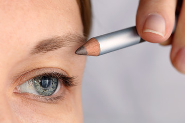 Young beautiful woman applying eyebrow pencil close up. Beauty, make up concept