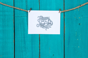 Happy New Year sign hanging on rope with antique teal blue wood backgound