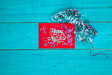 Happy New Year sign with colorful ribbon on antique teal blue wood background