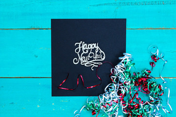 Happy New Year sign with ribbon on wood background