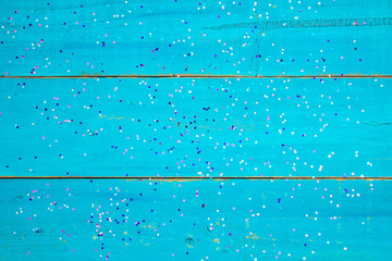 Teal blue wood background with colorful confeffi