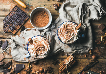 Hot chocolate with whipped cream and cinnamon sticks served with anise, nuts and cocoa powder on rustic wooden background, top view, horizontal composition