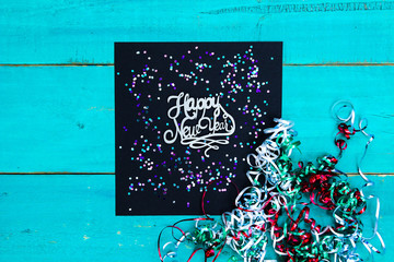 Happy New Year sign with ribbon and confetti