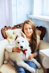 girl holds a dog in the room. The concept of friendship