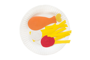 roasted chicken leg, french fries, ketchup and mayonnaise made of colored paper on a disposable plate. the concept of junk food. isolated on white background, top view