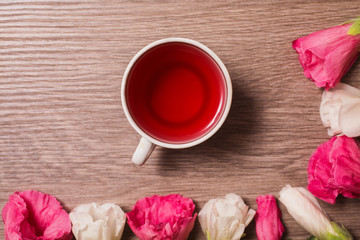 Red and white flowers and red tea in a white mug lying on the wo