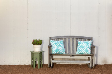 Colorful Pillows on wooden bench on pine bark.
