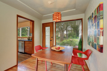 Dining area interior with red chairs and exit to the back yard.