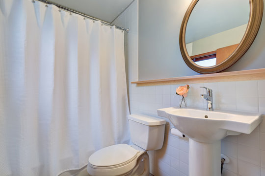 White clean bathroom with washbasin stand and a toilet.