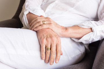 Close up of older woman's hands in relaxed position (cropped and selective focus)