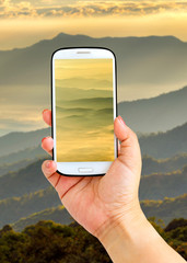 Smartphone photographing close up layer of mountains and mist in sunrise time, Landscape at Doi Luang Chiang Dao, High mountain in Chiang Mai Province, Thailand