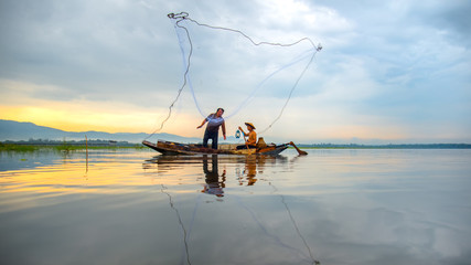 Fisherman of Bangpra Lake in action when fishing in the sunshine morning, Thailand, select focus