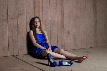 Beautiful teen girl in formal blue dress seated against a wall