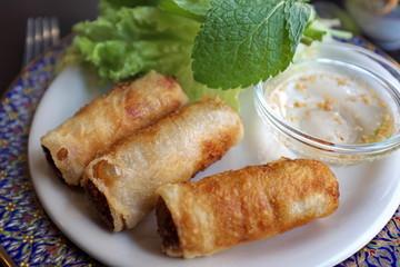 Petits nems avec salade, feuilles de menthe et sauce.