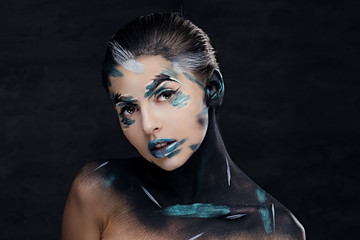 A woman with colorful make up and painted art on a neck.
