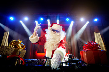 DJ Santa Claus mixing up some Christmas event.  Disco light arou