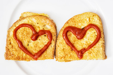 Two fried breads in the egg with hearts of ketchup, valentine